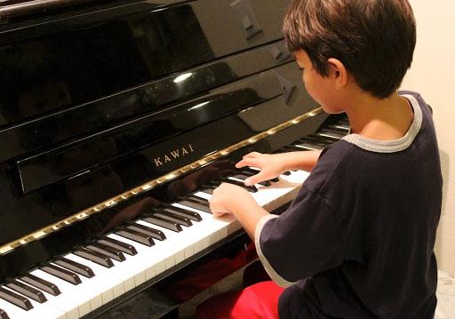 Dziecko uczące się gry na fortepianie